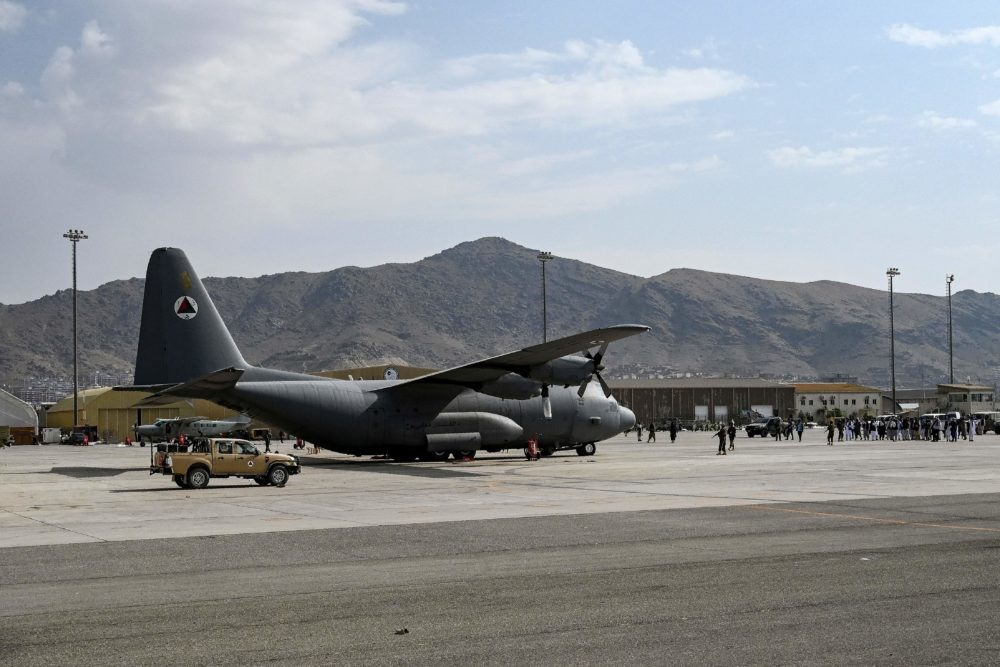 Taliban Badri special force fighters stand guard next to a Afghan Air Force aircraft at the airport in Kabul (Wakil Kohsar/Getty Images)