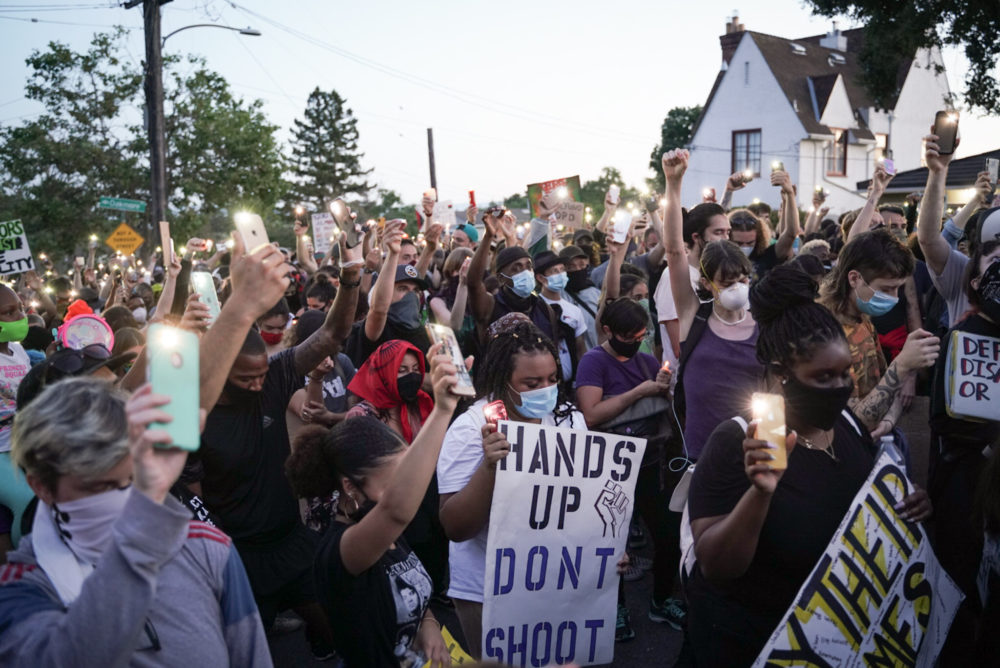 Demonstrators light candles during a 2020 protest to defund the Oakland Police Department. (Sarahbeth Maney/The San Francisco Chronicle via Getty Images)