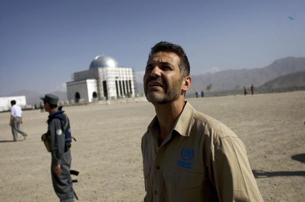 """Afghan-American author Khaled Hosseini watches Afghan boys fly kites during a United Nations sponsored visit in Kabul on September 14, 2009.  Hosseini, the Afghan-American author of bestselling novel """"The Kite Runner"""", flew kites with boys on a Kabul hilltop, hailing development as the key to crushing Taliban rebels. (David Furst/AFP via Getty Images)"""