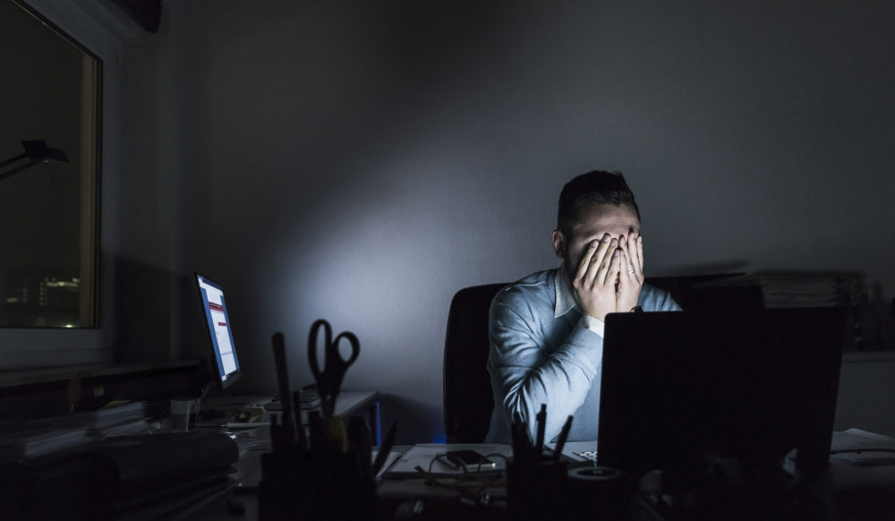 Exhausted businessman sitting at desk in office at night (Getty Images)