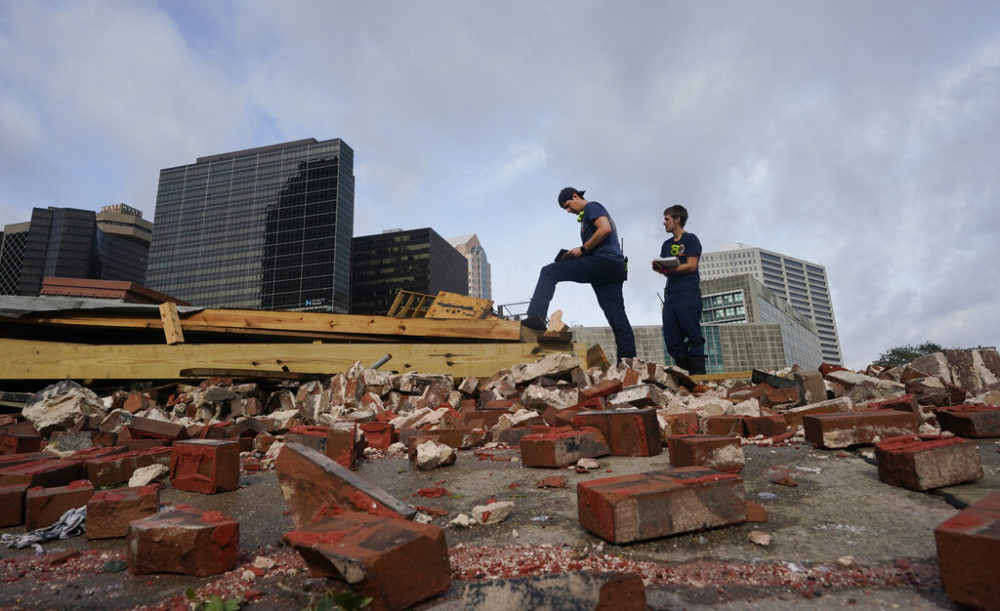 New Orleans Firefighters assess damage as they look through debris after a building collapsed from the effects of Hurricane Ida, Monday, Aug. 30, 2021, in New Orleans, La. All of New Orleans lost power right around sunset Sunday as the hurricane blew ashore on the 16th anniversary of Katrina. (Eric Gay/AP)