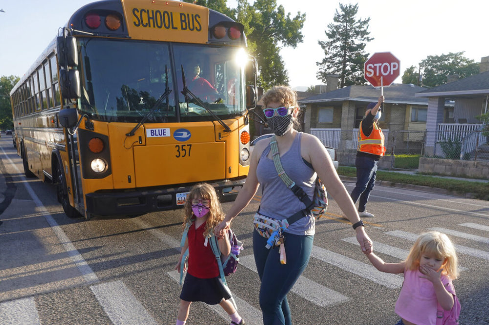 Sandra Young arrives at Whittier Elementary School with her daughters Baylin, 5, and Paytin, 2, on Tues., Aug. 24, 2021, in Salt Lake City. Kids in Salt Lake City are headed back to school wearing masks after the mayor issued a mandate order despite heavy restrictions on mask mandates imposed by the GOP-dominated Legislature. (Rick Bowmer/AP)