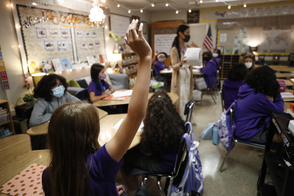 Students ask questions in the CORE History and English class of teacher Jessica Valera at the Girls Academic Leadership Academy: Dr. Michelle King School for STEM students in Los Angeles on the first day of in-class instruction on August 16. (Al Seib/Los Angeles Times via Getty Images)