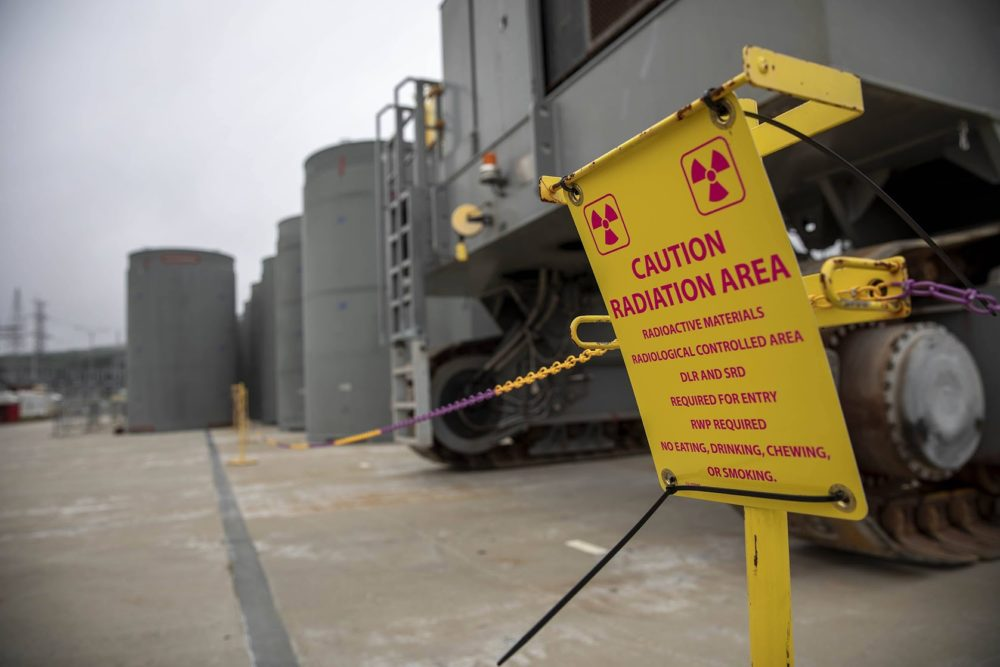 A sign by casks containing spent fuel on a concrete pad near the Pilgrim reactor building, warns of the presence of radioactive materials. (Robin Lubbock/WBUR)