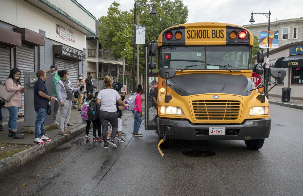 Families watch as kids board a school bus on Geneva Ave. in Dorchester for the first time this school year. (Robin Lubbock/WBUR)