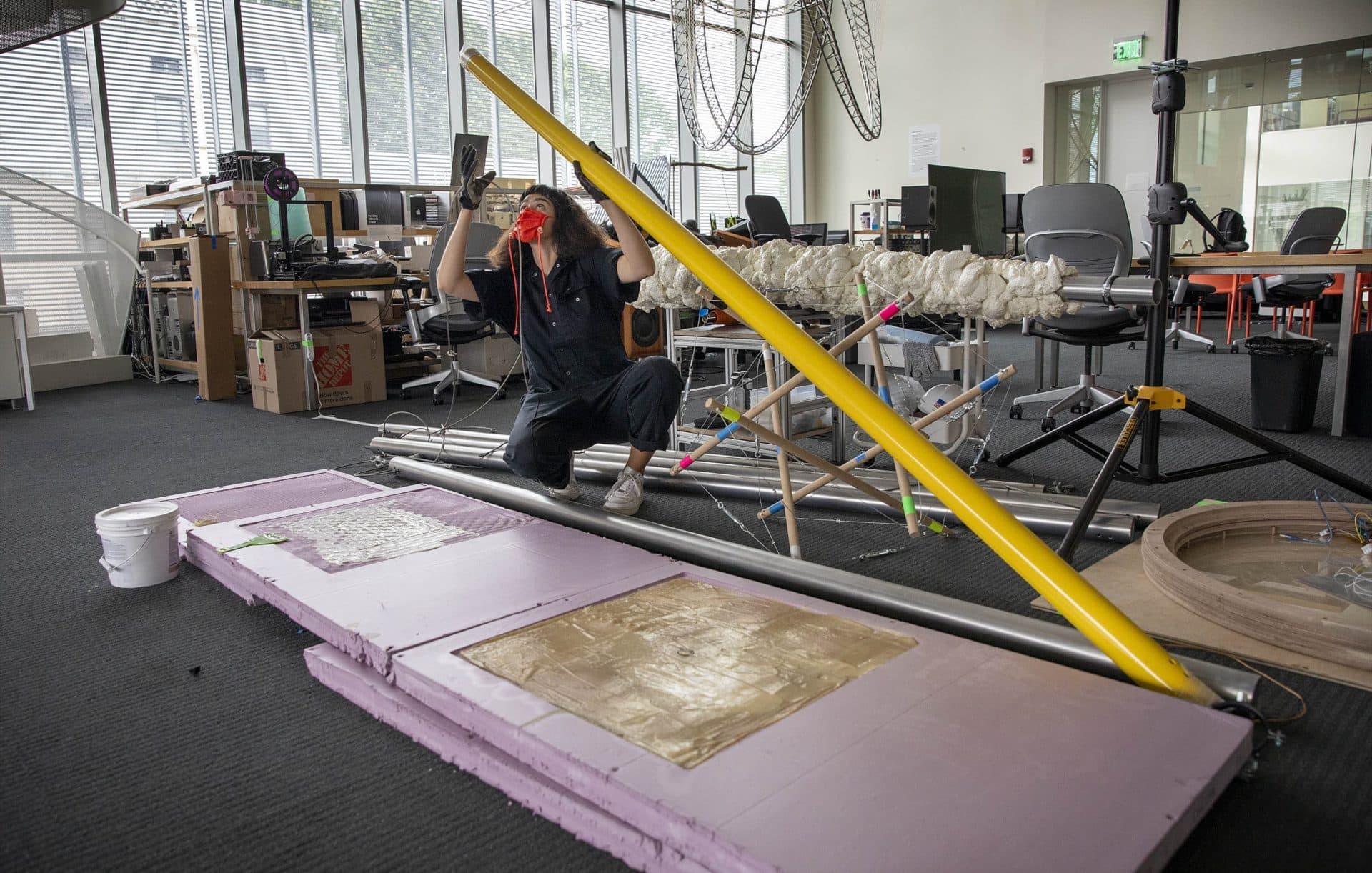 "Artist Nicole L'Huillier examining the unassembled elements of her installation ""Membranes."" (Robin Lubbock / WBUR)"