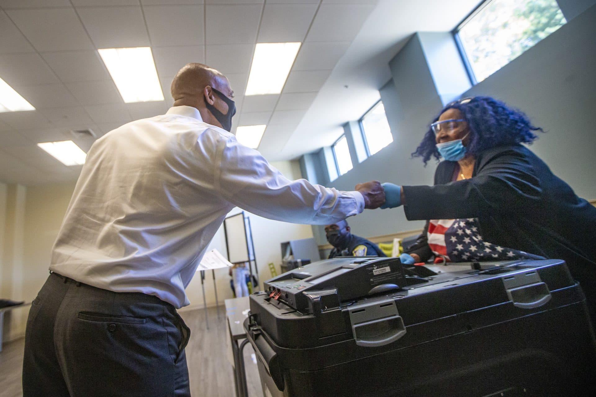 John Barros choca con la trabajadora electoral voluntaria Eileen Kenner después de emitir su voto en Uphams Corner.  (Jesse Costa / WBUR)