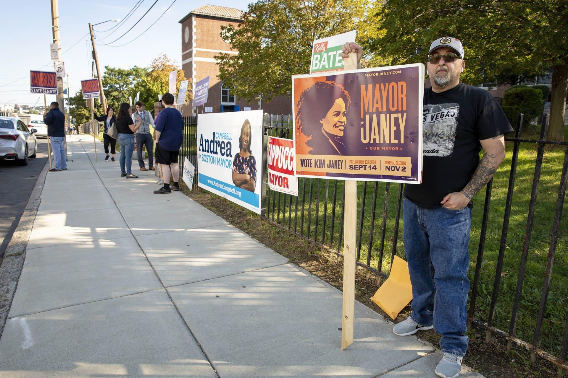 """Larry Tinnirello sostiene un letrero que dice """"Vote Kim Janey"""" afuera del colegio electoral de East Boston High School.  (Robin Lubbock / WBUR)"""