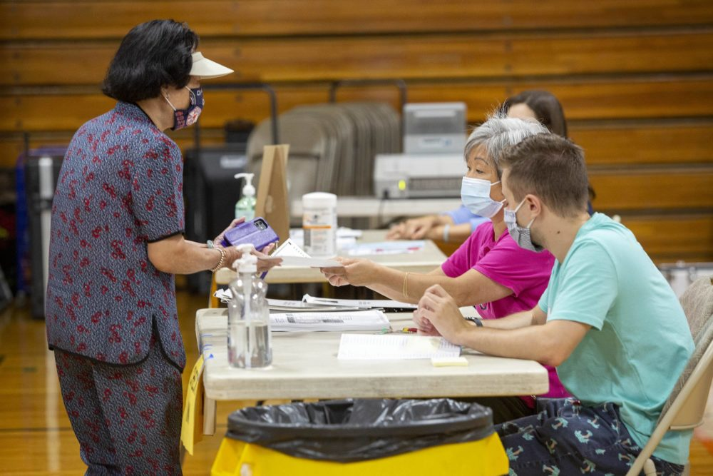 A voter receives a ballot as voting gets under way at the Wang YMCA polling station in Boston. (Robin Lubbock/WBUR)
