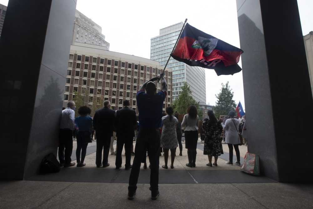 Jean Alfred Sandaire waves a Haitian national flag and a Black Lives Matter flag during the Solidarity with Haiti demonstration at John F. Kennedy Federal Building in Downtown Boston. (Jesse Costa/WBUR)