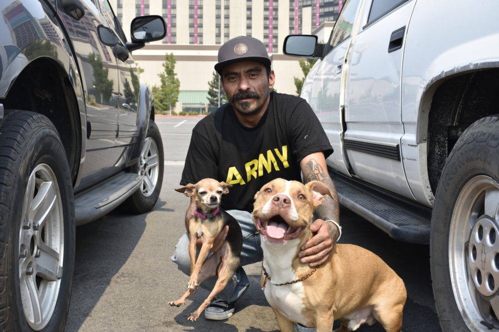 South Lake Tahoe resident Jose Mora was relocated from the American Red Cross' evacuation center at the Carson City Community Center to the Reno-Sparks Convention Center with his family and two dogs, Lady (right) and Woody, on Sept. 1, 2021. (Lucia Starbuck/KUNR Public Radio)