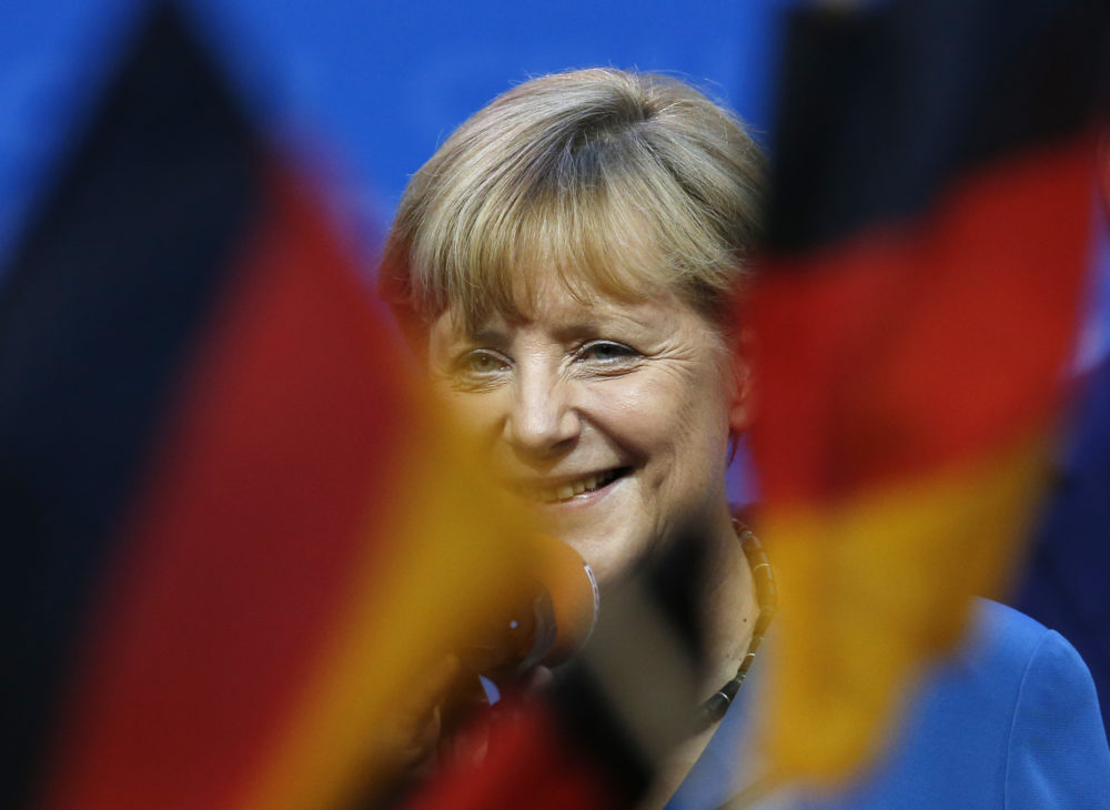 German chancellor Angela Merkel smiles behind German flags at the party headquarters in Berlin, Sunday, Sept. 22, 2013. (Michael Sohn/AP)