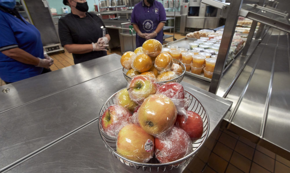 Individually wrapped apples and oranges and fruit in plastic cups are seen at the cafeteria line of the Norris Middle School in Omaha, Neb., on July 29, 2020. (Nati Harnik/AP)