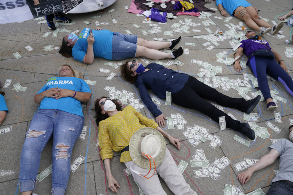 Protesters, including photographer and activist Nan Goldin, center right, stage a die-in and have their shapes traced on the sidewalk outside the courthouse where the Purdue Pharma bankruptcy is taking place in White Plains, N.Y., Aug. 9, 2021. (Seth Wenig/AP)