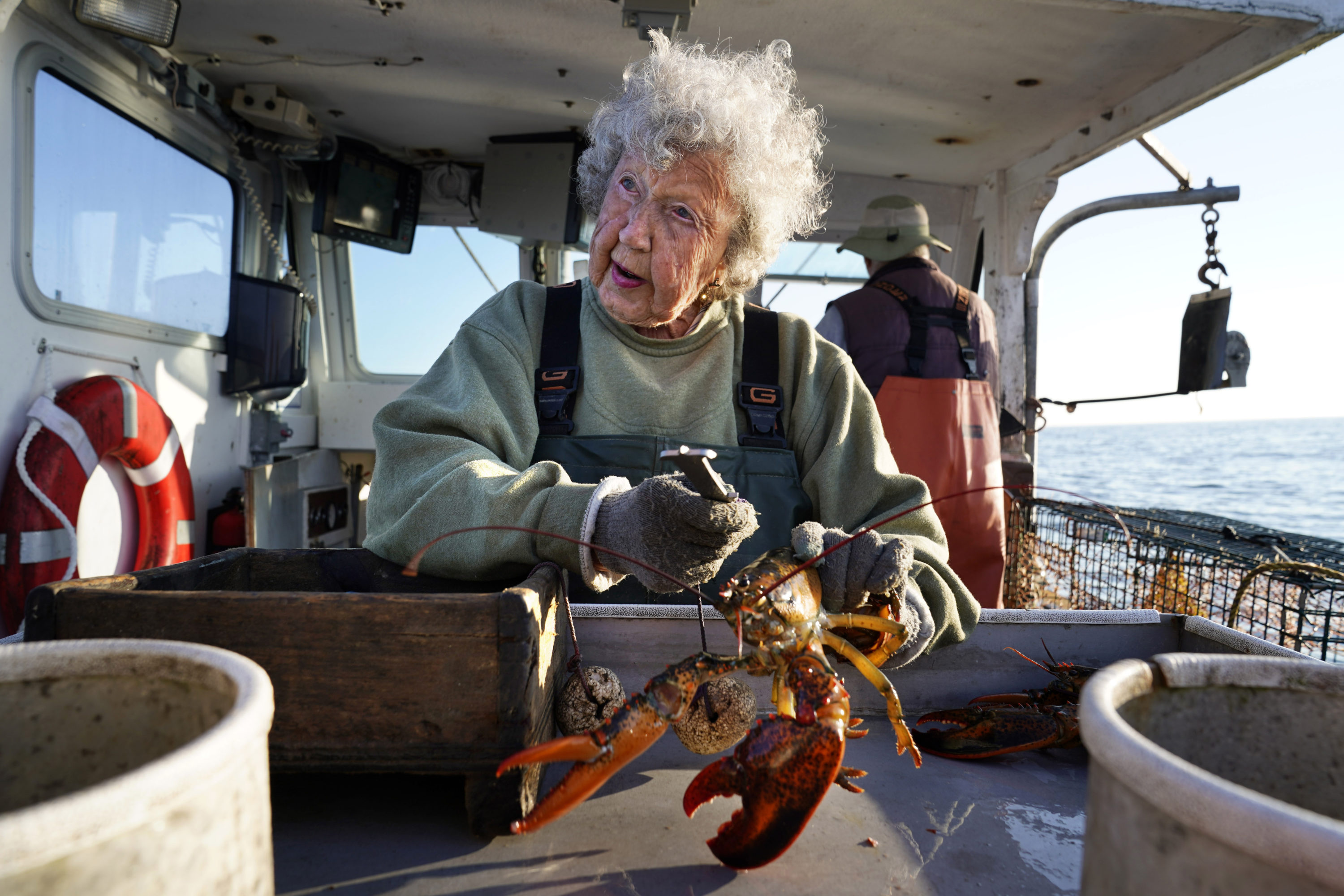 Virginia Oliver, age 101, works as a sternman, measuring and banding lobsters on her son Max Oliver's boat, Aug. 31, 2021, off Rockland, Maine. The state's oldest lobster harvester has been doing it since before the onset of the Great Depression. (Robert F. Bukaty/AP)