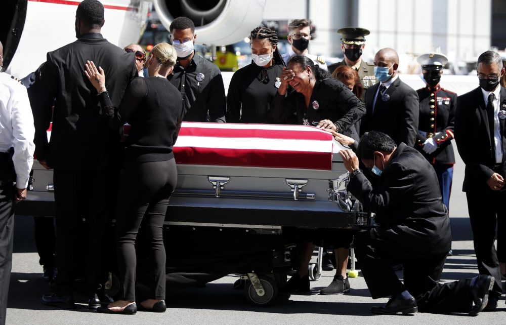 Family members of U.S. Marine Sgt. Johanny Rosario Pichardo are emotional as the casket with Pichardo arrives at Logan Airport on Saturday, Sept. 11, 2021.  Pichardo died in the Aug. 26 suicide bombing near the Kabul airport where people were being evacuated amid the Taliban takeover of Afghanistan.  (Jonathan Wiggs /The Boston Globe via AP, Pool)