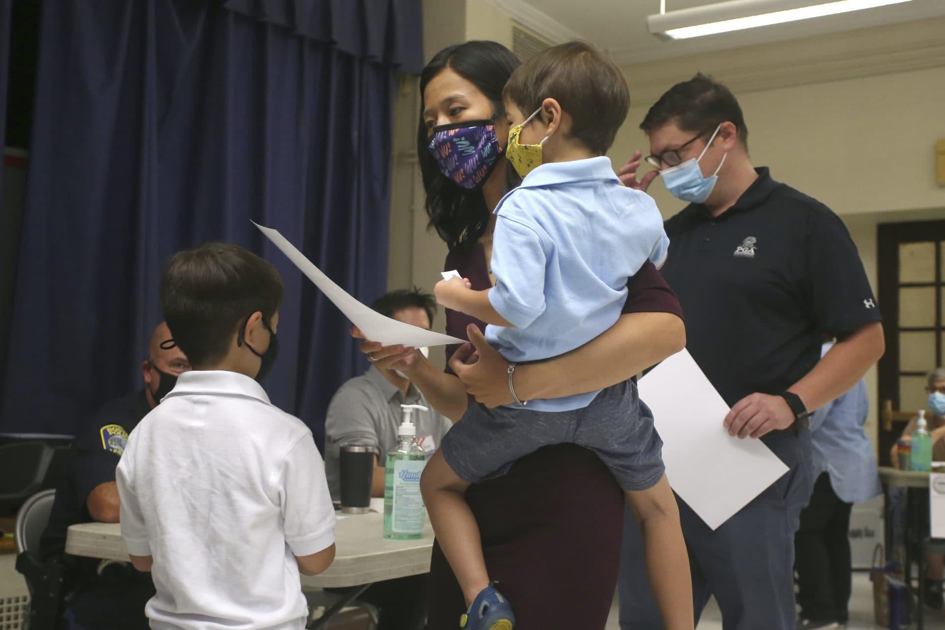 La candidata a la alcaldía de Boston, Michelle Wu, sostiene a su hijo Cass, de 4 años, emite su voto en la carrera por la alcaldía el día de las elecciones, junto con su esposo Conor Pewarski, a la derecha, y su otro hijo Blaise, a la izquierda, de 6 años, en la escuela primaria Phineas Bates. Escuela en Boston, 14 de septiembre de 2021 (Stew Milne / AP)