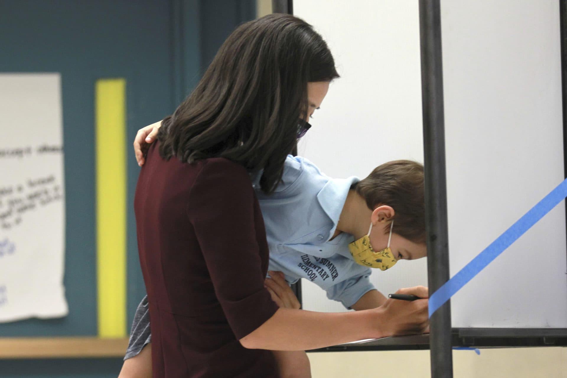Michelle Wu llena su boleta en la carrera por la alcaldía mientras sostiene a su hijo Cass, de 4 años, en la escuela primaria Phineas Bates en Boston.  (Stew Milne / AP)