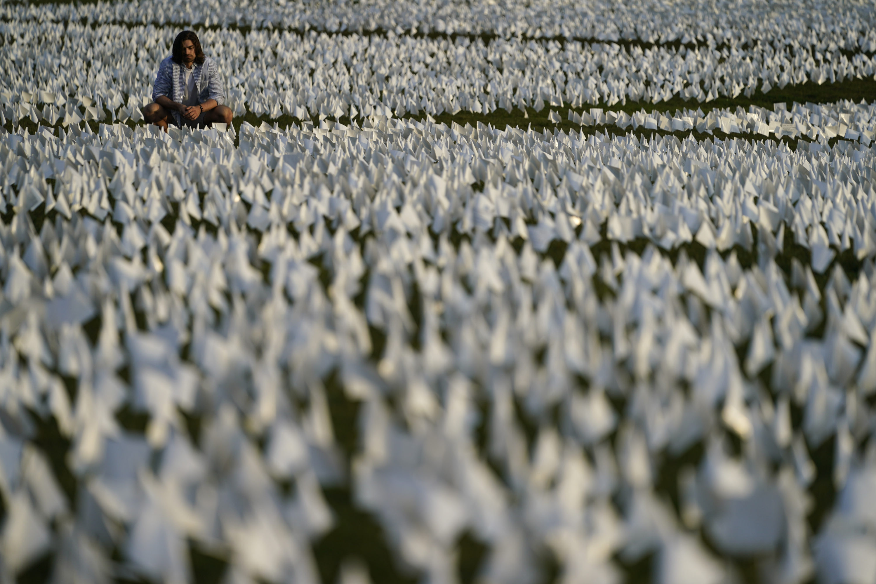 """A person looks at white flags that are part of artist Suzanne Brennan Firstenberg's temporary art installation, """"In America: Remember,"""" in remembrance of Americans who have died of COVID-19, on the National Mall in Washington on Sept. 17, 2021. (Brynn Anderson/AP)"""