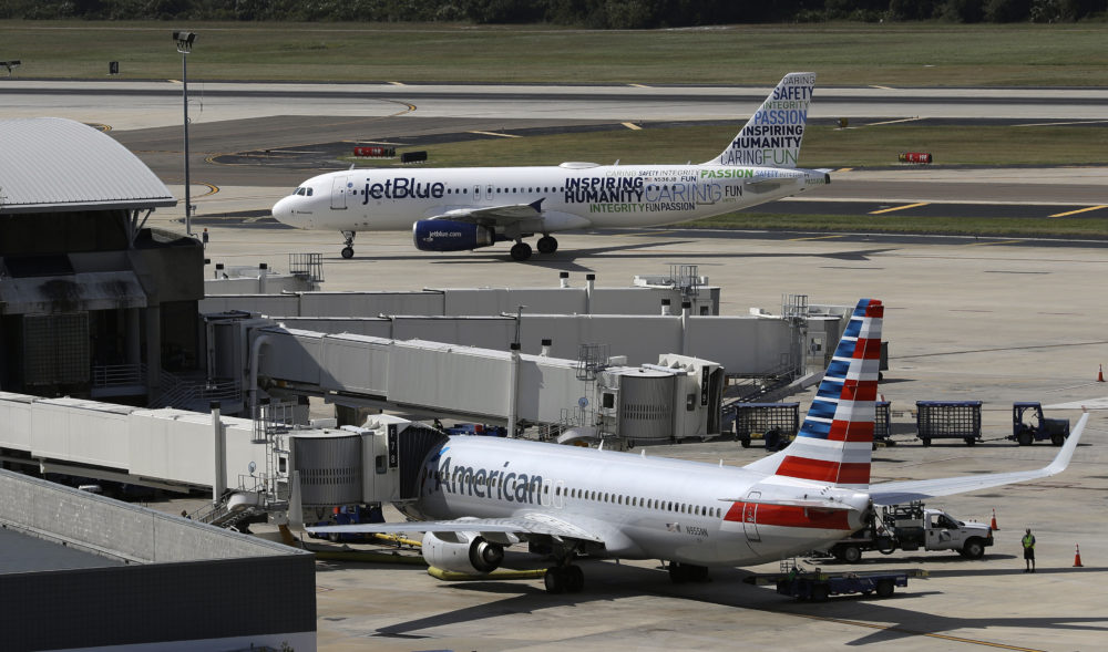 A JetBlue Airbus taxis to a gate as an American Airlines jet is seen parked at its gate at Tampa International Airport in Florida. (Chris O'Meara/AP)