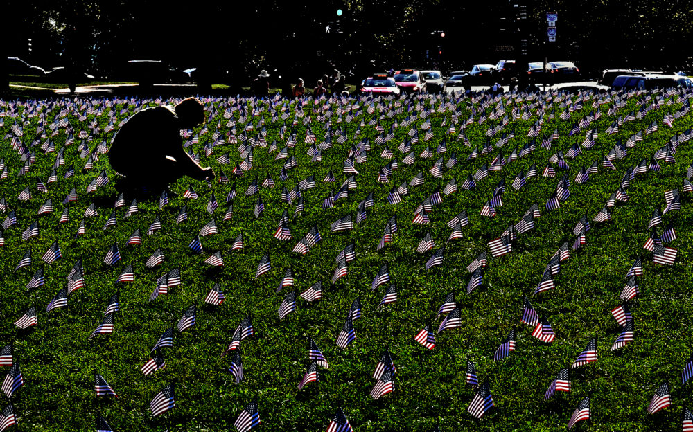 More than 5,000 American flags were planted on a grassy area of the National Mall, each representing a veteran or a service member who died by suicide through early October 2018, an average of 20 suicides per day. Ryan Conklin straightens some flags at the site. Conklin is an Iraq and Afghanistan (U.S. Army) veteran who lost several comrades and a close friend to suicide. (Michael S. Williamson/The Washington Post via Getty Images)