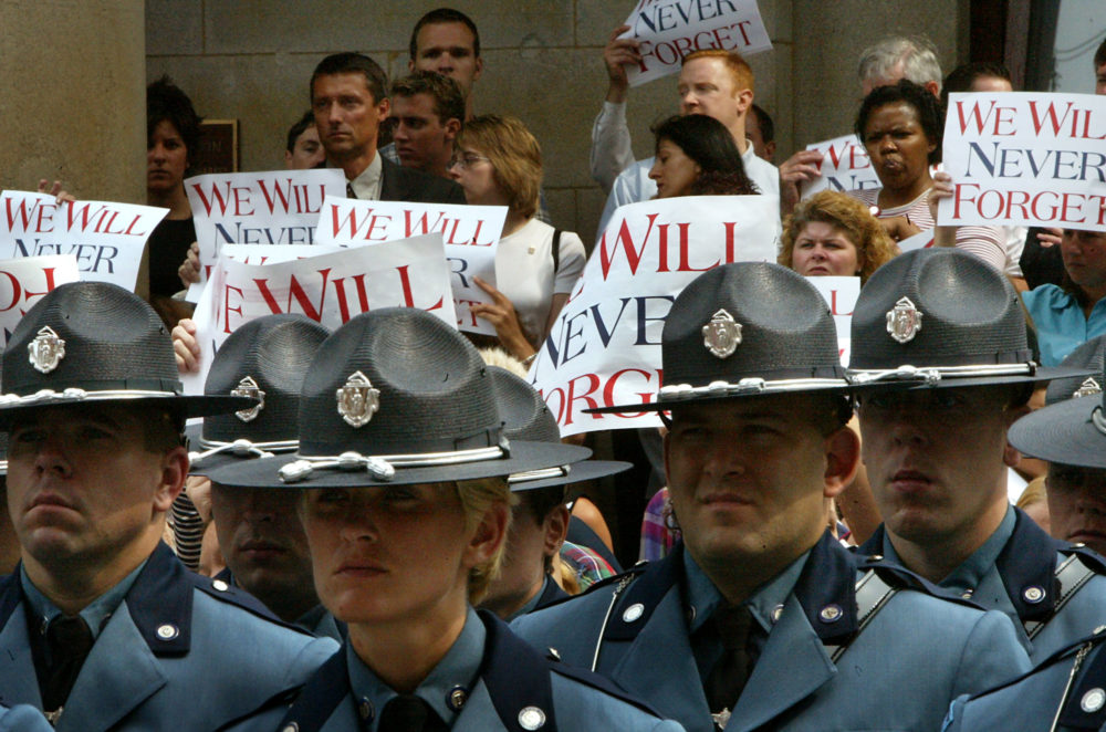Passersby hold up signs as an Honor Guard of State Troopers stands at attention outside Faneuil Hall, where a Massachusetts Remembrance Ceremony was held in 2002 to mark the one-year anniversary. (Barry Chin/The Boston Globe via Getty Images)