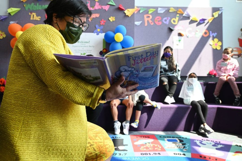 """Los Angeles Unified School District (LAUSD) interim Superintendent Megan Reilly reads a book called """"First Day Jitters"""" to students in the library at Kim Elementary School on the first day of the school year, in Los Angeles, California, August 16, 2021. (Robyn Beck/AFP/Getty Images)"""