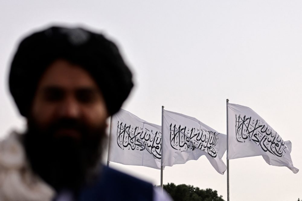A Taliban fighter is pictured against the backdrop of Taliban flags installed at the Hamid Karzai International Airport in Kabul on Sept. 11, 2021. (Karim Sahib/AFP via Getty Images)