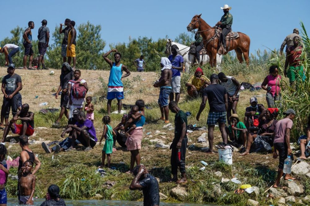 A United States Border Patrol agents on horseback look on as Haitian migrants sit on the river bank near an encampment on the banks of the Rio Grande near the Acuna Del Rio International Bridge in Del Rio, Texas on Sept. 19, 2021. (Paul Ratje/Getty Images)