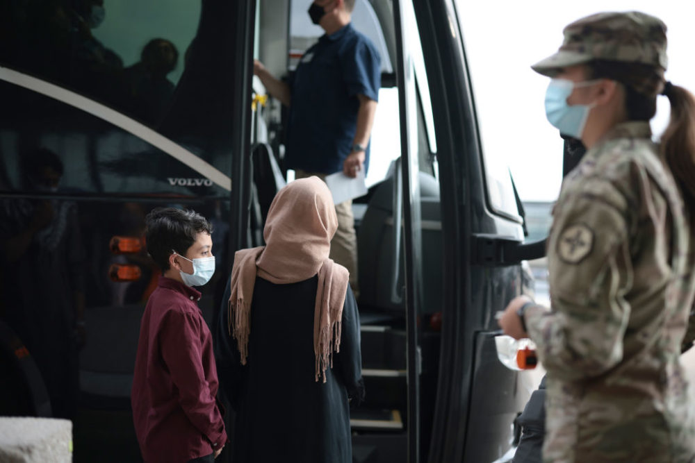 Refugees board a bus at Dulles International Airport in Virginia that will take them to a refugee processing center after being evacuated from Kabul following the Taliban takeover of Afghanistan on Aug. 31, 2021. (Anna Moneymaker/Getty Images)