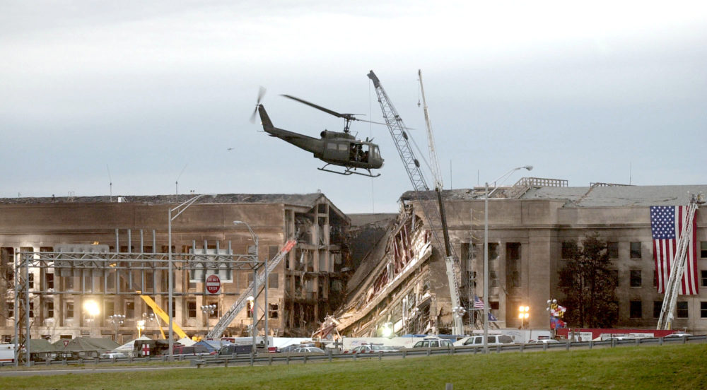 A military helicopter flies in front of the Pentagon September 14, 2001 in Arlington, Virginia at the impact site where a hijacked airliner crashed into the building.  (Stephen J. Boitano/Getty Images)