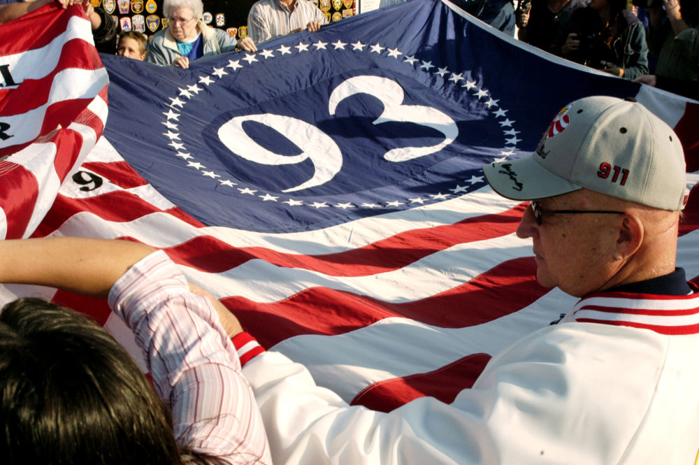 Visitors assist in unfolding a giant flag at a temporary memorial overlooking the crash site in Shanksville, Pennsylvania. The plane crashed Sept. 11, 2001, into a rural field from the presumed target of the nation's capital, killing 40 people. (Archie Carpenter/Getty Images)