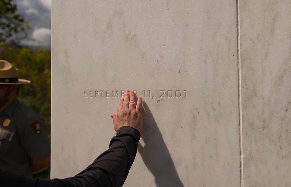 A visitor traces the date etched in a marble slab on the Wall of Names at the Flight 93 National Memorial in Shanksville, Pa., in 2016. United Airlines Flight 93 crashed into a field outside Shanksville, Pa., with 40 passengers and four hijackers aboard on Sept. 11, 2001. (Jeff Swensen/Getty Images)