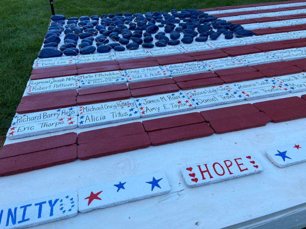 An American flag memorial, created by younger volunteers at an event on the Rose Kennedy Greenway, bears the names of 9/11 victims with ties to Massachusetts. (Quincy Walters/WBUR)