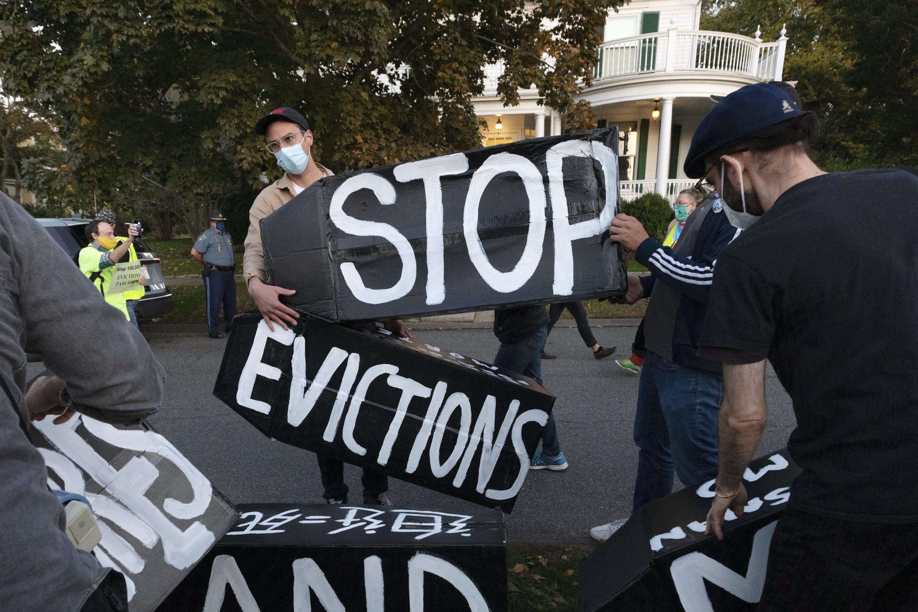In this Oct. 14, 2020, file photo, housing activists erect a sign in front of Gov. Charlie Baker's house in Swampscott, Mass. (Michael Dwyer/AP)