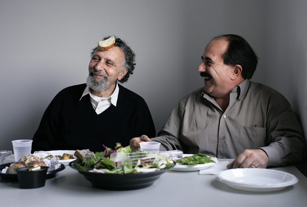 """Tom and Ray Magliozzi, better known as """"Click and Clack,"""" the co-hosts of the nationally syndicated talk show, """"Car Talk."""" Here, they eat lunch with members of their production crew after a recording session on Dec. 22, 2004 at WBUR. (Dina Rudick/The Boston Globe via Getty Images)"""