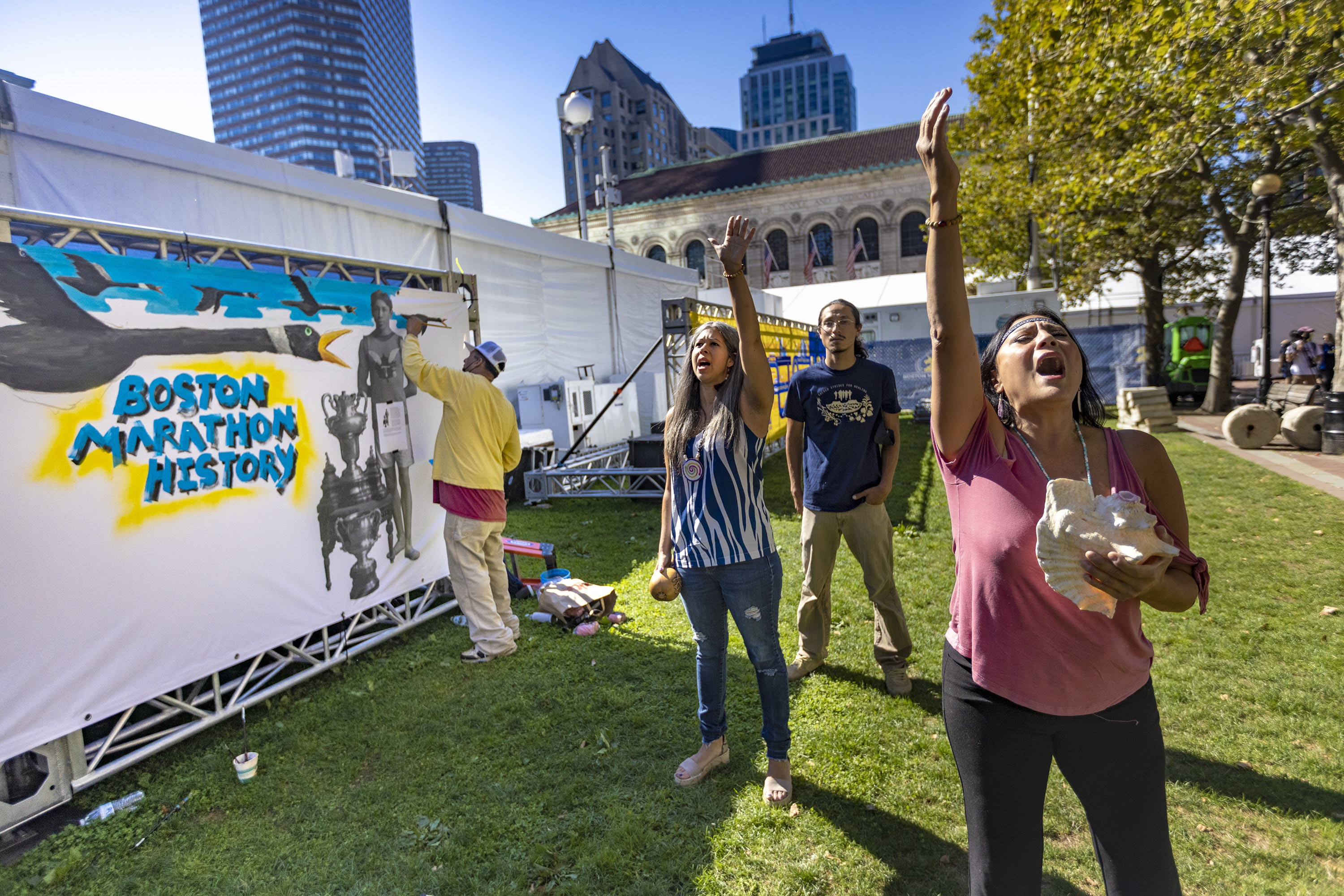 Chali'Naru Dones, right, and Darlene Flores, co-founders of the Indigenous Peoples' Day Committee in Newton, perform a healing song as artist Robert Peters paints a mural illustrating Indigenous history in the Boston Marathon near the finish line in Copley Square. (Jesse Costa/WBUR)