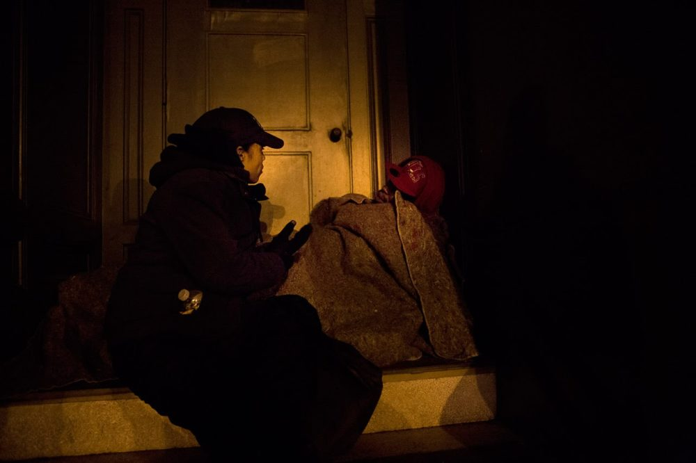 Elisabeth Jackson, executive director of Bridge Over Troubled Waters, asks a homeless person sleeping in a doorway on Bromfield St. if he needs any assistance during Boston's annual homeless census in 2013. (Jesse Costa/WBUR)