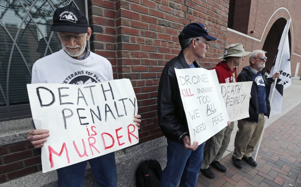 """A group from """"Veterans for Peace"""" picketed outside the Moakley Federal Courthouse as jurors deliberated in the penalty phase of the trial of Boston Marathon bomber Dzhokhar Tsarnaev, Friday, May 15, 2015. (Charles Krupa/AP)"""
