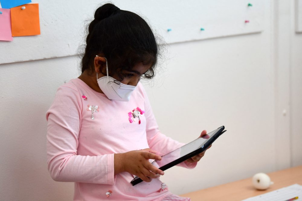 A pupil, wearing a protective face mask, works with an iPad during a summer project. (Ina Fassbender/AFP via Getty Images)